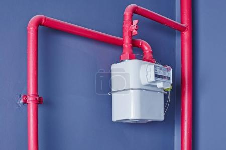 Gas meter on a grey wall with pink piping
