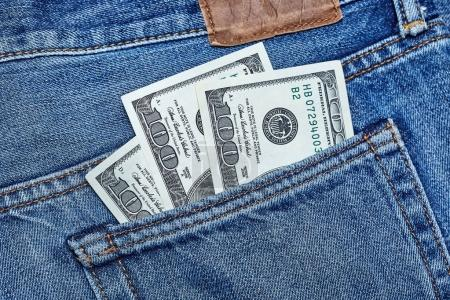 One hundred dollar banknotes in a jeans pocket close-up