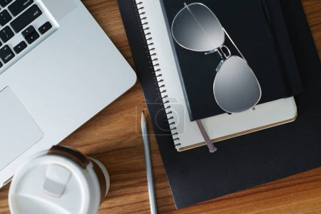 Ordinary objects on the table: coffee cup, glasses, pencil, notebook and paper with laptop near by. Top view