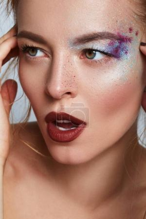 Beauty Fashion model girl portrait with creative colorful makeup, red lips and trendy fashion look. Beauty trends. Isolated on white.