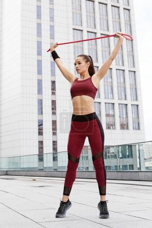 Fitness sporty woman during outdoor exercises workout. Beautiful fit Girl with  fitness elastic band. Fitness model outdoors. Weight Loss. Healthy lifestyle. Sporty healthy female.
