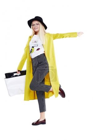 Pretty young women in yellow coat and black hat holding shopping bag isolated on white background. Fashion portrait of a blond stylish women posing at studio in fashionable clothes.