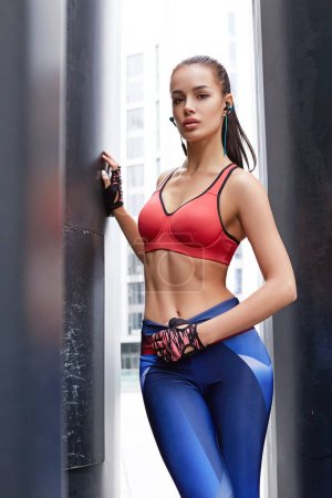 Fitness sporty woman with headphones during outdoor exercises workout. Beautiful fit Girl in sport wear. Fitness model outdoors. Weight Loss. Healthy lifestyle. Sporty healthy female.