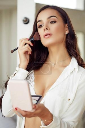 Young beautiful brunette women doing natural morning makeup using brush and looking in mirror