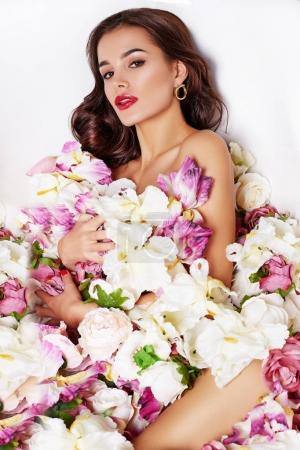 Spa beauty model girl taking flower bath, spa and skin care concept. Beauty young Woman with bright makeup and pink flowers relaxing in bath