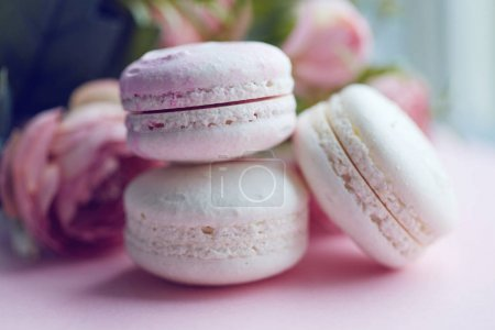 Colorful pastel macaroons on the pink table with flower background