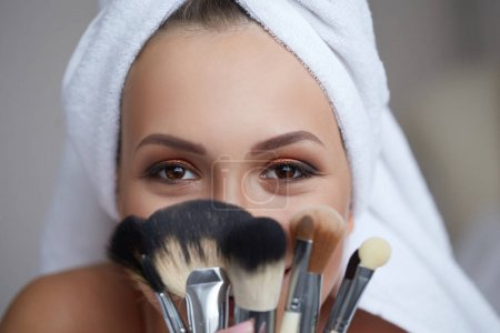 Young beautiful smiling woman with towel on her head holding make-up brushes in her hands.