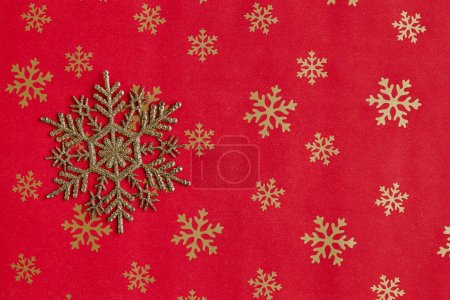 Christmas still life. Gold snowflakes and decorative Christmas ornaments on a red background.