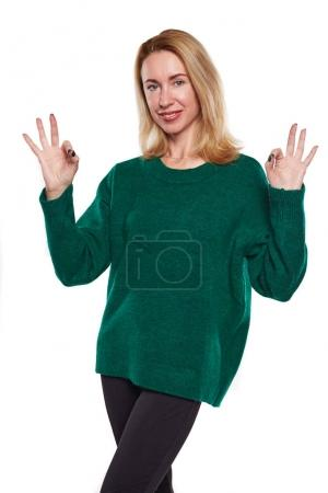 Photo for Blond woman gesturing ok sign with both hands. Woman in green sweater approves something. Isolated on white background. - Royalty Free Image