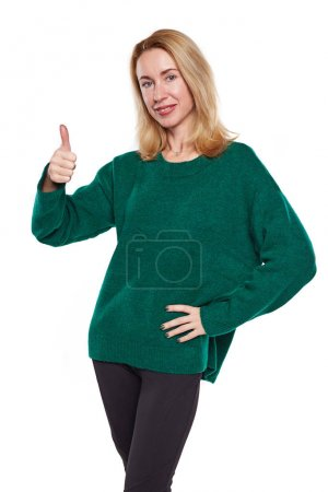 Photo for Blond woman gesturing ok sign. Woman in green sweater approves something. Isolated on white background. - Royalty Free Image