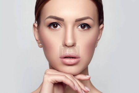 Beauty Woman face Portrait Close-up. Beautiful Spa model Girl with Perfect Fresh Clean Skin. Brunette  female looking at camera touches own face. Youth and Skin Care Concept. Horizontal
