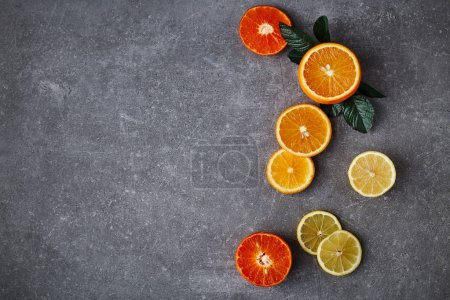 Photo for Orange slices with green leafs composition on a grey background. Top view - Royalty Free Image