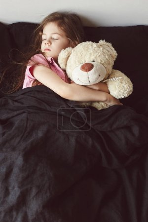 Portrait of a little girl sleeping in the bed in her bedroom with a big teddy bear. Girl with a plush toy bear.