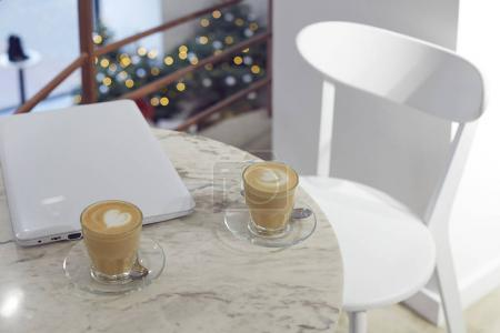 Photo for Coffee and closed white laptop on the table in cafe - Royalty Free Image