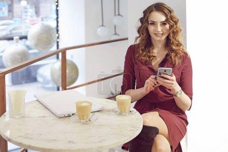 Photo pour Femme souriante dans le café à l'aide de téléphone portable et envoyer des SMS dans les réseaux sociaux, siégeant seul et boire du café - image libre de droit