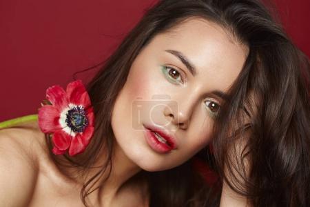 Photo pour Belle fille brune avec des yeux verts maquillage et peau fraîche posant à fond rouge avec fleur, spa beauté, concept de soins de la peau, produit bio. - image libre de droit