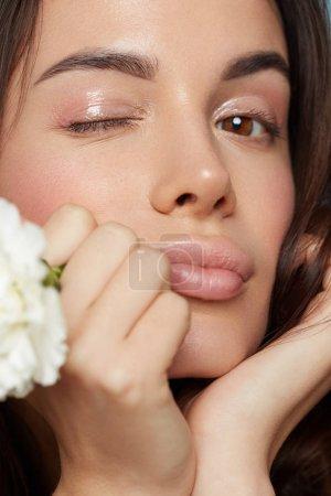 Photo pour Gros plan d'une magnifique jeune fille brune avec un maquillage nu et peau fraîche posant avec une fleur oeillet blanche dans sa main toucher son visage. Concept de soins, spa beauté, produit bio de la peau. - image libre de droit