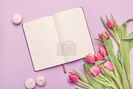 Cropped view of planner with tulips and macaroon cookies on a pink background. Woman elegant desktop.