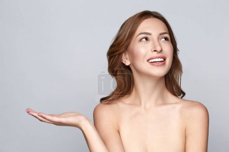 Beauty Spa Woman with perfect skin. Beautiful Smiling Brunette Spa Girl showing empty copy space on the open hand palm for text. Proposing a product. Gestures for advertisement. Grey  background