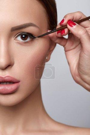 Woman doing eye make-up using black eye liner. Beautiful woman close-up. Beauty skin healthy and perfect makeup.