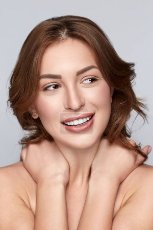 Beautiful face of a young Beautiful Spa model Girl with Perfect Fresh Clean Skin. Brunette  female touches own shoulders. Youth and Skin Care Concept.