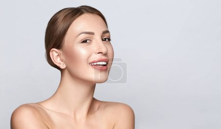 Beautiful smiling girl with clean clear skin, natural make-up, and white teeth on grey background. Beauty and spa concept. Healthy skin.
