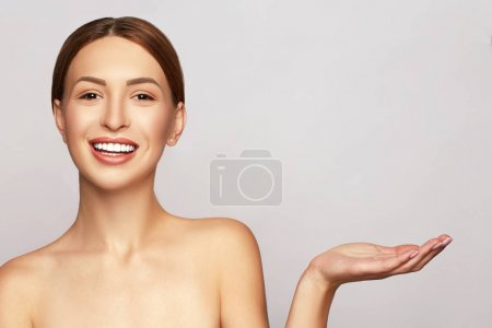 Beauty Spa Woman with perfect skin Portrait. Beautiful Smiling Brunette Spa Girl showing empty copy space on the open hand palm for text. Proposing a product. Gestures for advertisement. Grey background