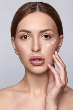 Woman applying foundation. Skin tone cream dots on woman face. Beautiful woman portrait beauty skin healthy and perfect makeup.