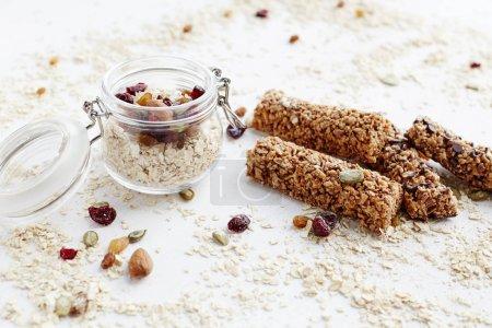 Photo pour Barre granola et flocons d'avoine. Collation de dessert sucré biologique sain. Barre de céréales granola avec les noix, les fruits et les baies sur un tableau blanc. - image libre de droit