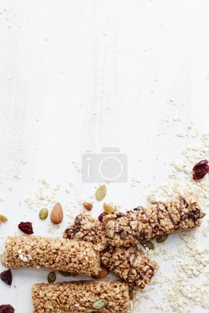 Photo for Granola bar. Healthy organic sweet dessert snack. Cereal granola bar with nuts, fruit and berries on a white wooden table. Top view. - Royalty Free Image