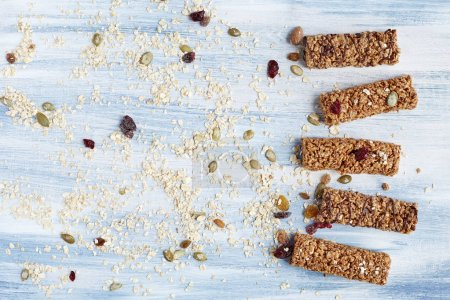 Photo for Granola bar. Healthy organic sweet dessert snack. Cereal granola bar with nuts, fruit and berries on a blue wooden table. Top view. - Royalty Free Image