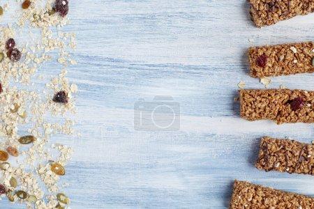 Photo pour Barre granola. Collation de dessert sucré biologique sain. Barre de céréales granola avec les noix, les fruits et les baies sur une table en bois bleue. Vue de dessus. - image libre de droit