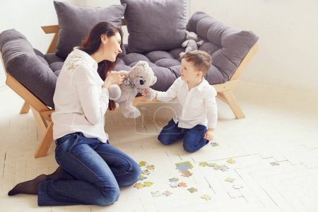 Happy Mother and son sitting on floor and playing with teddy bear. Maternity concept. Parenthood. Motherhood