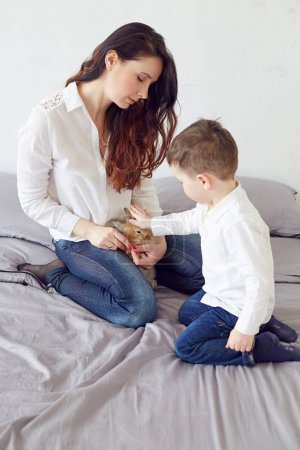 Happy Mother and son sitting on bed and playing with bunny. Maternity concept. Parenthood. Motherhood