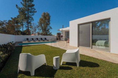 Photo pour Maison moderne avec piscine de jardin et terrasse en bois - image libre de droit
