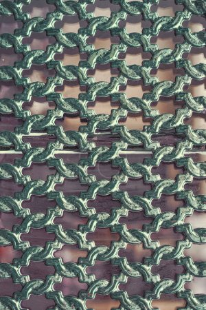 Photo for Piece of wrought iron grating on window. Vintage metal openwork grille in green, abstract background. Close-up outdoors vertical image. Ancient floral pattern iron grid. - Royalty Free Image
