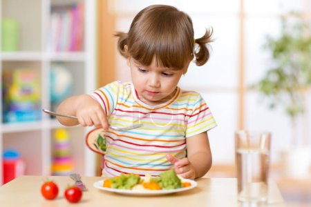 Child little girl has a lunch in kindergarten