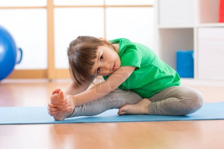 cute little girl stretching in gym