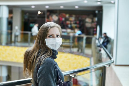 Young white woman in medical mask in a public space