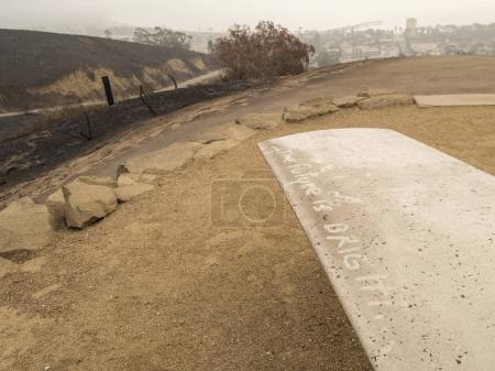 destroyed area with positive message on park bench after wildfire