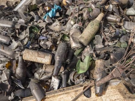 collection of trash and bottles with cans on ground