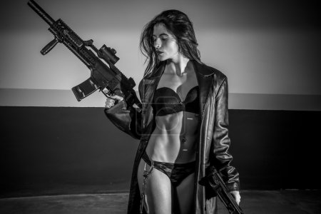 Photo for Fantasy brunette girl posing in long leather coat and holding weapons in garage - Royalty Free Image