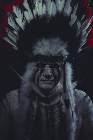 Indian chief posing in feathers headdress
