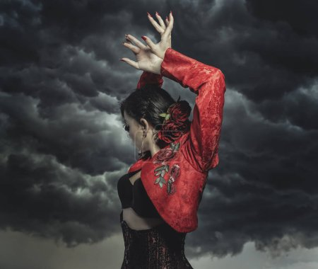 Photo for Spanish flamenco dancer with bun in hair and red coat with storm background in the sky - Royalty Free Image