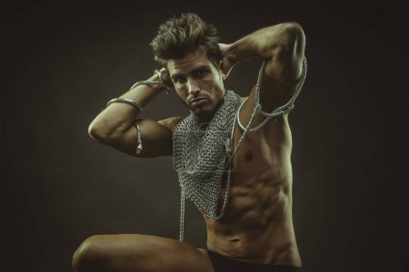 Elegant and muscular man with naked torso and chains