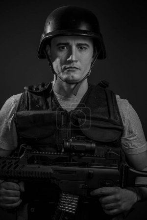 Paintball sport player in helmet and machine gun
