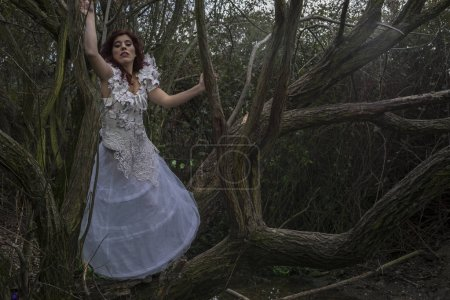 Beautiful red-haired woman in a forest with a cage
