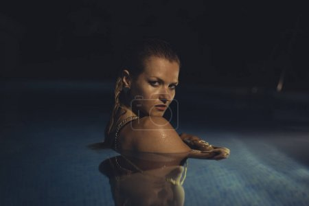 Beautiful blond woman in a night pool