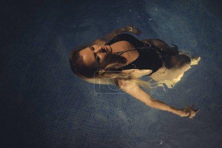 Beautiful blond woman in a night pool