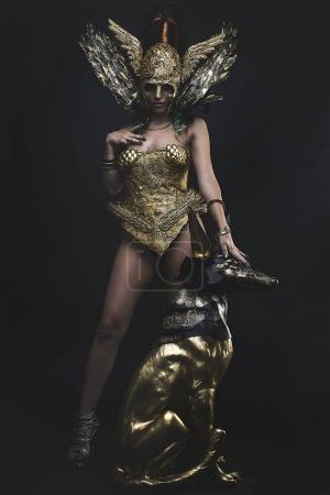 Photo pour Femme dans l'armure de la déesse avec statue égyptienne de seth - image libre de droit